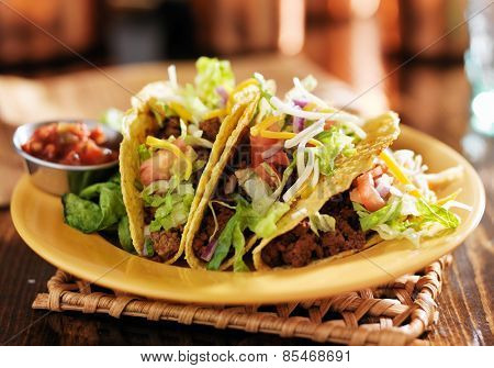 three beef mexican tacos with cheese and lettuce