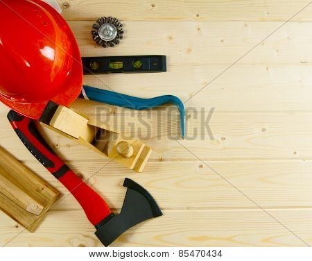 helmet, mount, axe, plane and other tool on a wooden background.