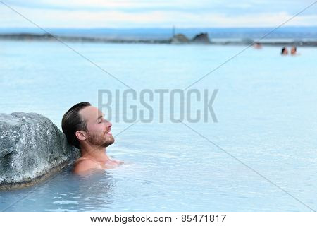 Geothermal spa. Man relaxing in hot spring pool on Iceland. Young man enjoying bathing relaxed in a blue water lagoon Icelandic tourist attraction.