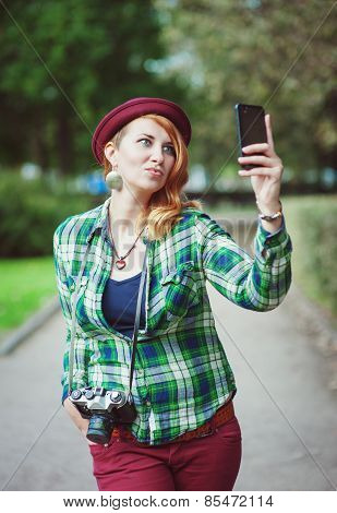 Hipster Redhead Woman In Hat Taking Picture Of Herself