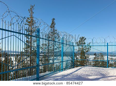 Closed Area Behind A Fence Topped With Barbed Wire