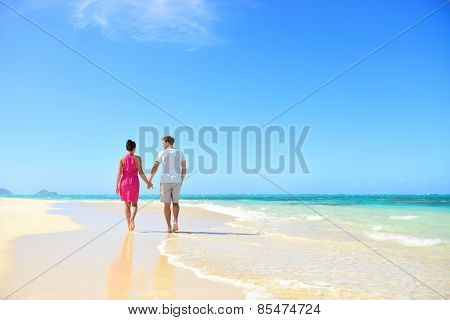 Honeymoon couple holding hands walking on perfect white sand beach. Newlyweds happy in love relaxing on summer holidays in sunny tropical paradise destination. Travel vacation concept.
