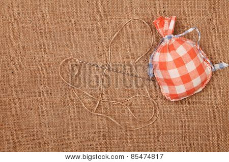 Red Bag And Needle On A Background Of Burlap