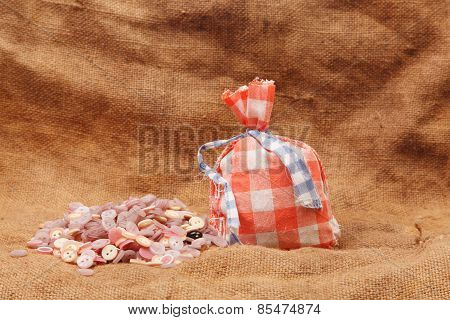 Red Bag And Buttons On A Background Of Burlap