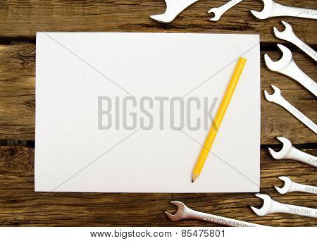 The Sheet of paper and wrenches on wooden background.