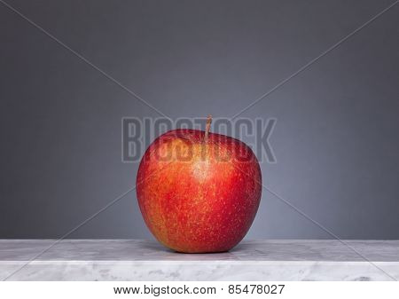 One Red Apple In Front Of Gray Background
