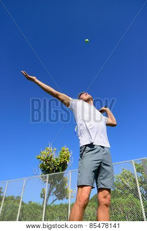 Tennis player serving playing outdoors sport. Man serve with throwing tennis ball up. Male athlete training practicing outdoors in summer.