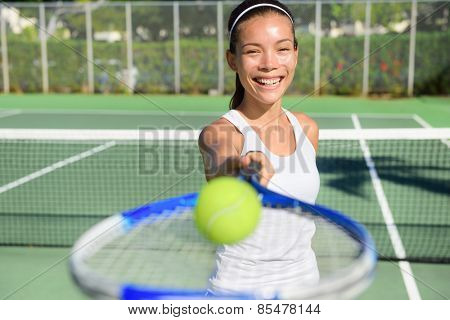 Tennis player portrait. Woman showing tennis ball and racket smiling happy. Female athlete inviting you to play tennis. Healthy active sport and fitness lifestyle concept outdoor.