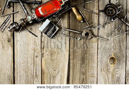 drill with drills on a wooden background.