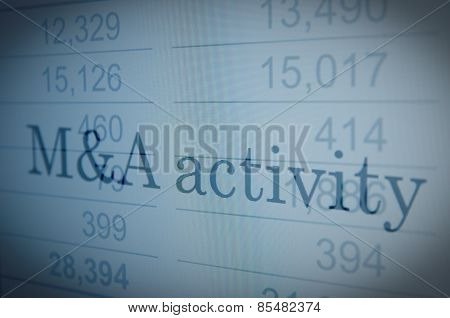 Inscription M&A activity on PC screen financial data visible on the background.