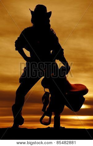 Silhouette Of Cowgirl Holding Saddle Straight On