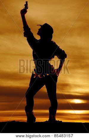 Silhouette Of Cowgirl Holding Up Gun Straight Up