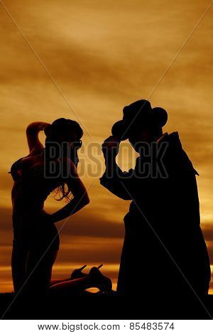 Silhouette Of Woman In Swimsuit Kneeling Looking Back At Cowboy