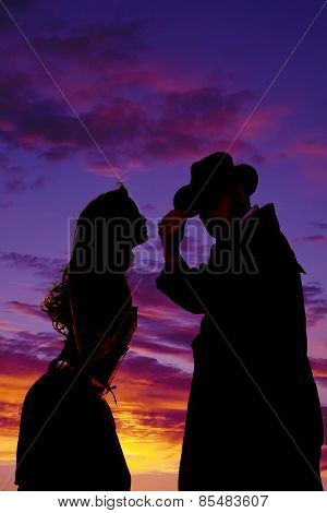 Silhouette Of Woman Leaning Toward Cowboy In Sunset