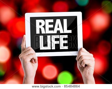 Tablet pc with text Real Life with bokeh background