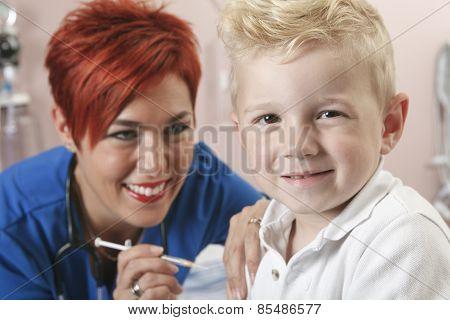 Small boy nurse gives him a shot.