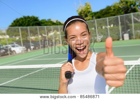Tennis player woman giving thumbs up happy and excited looking at camera. Successful winning female athlete living healthy active sport fitness lifestyle outdoors in summer on tennis court.