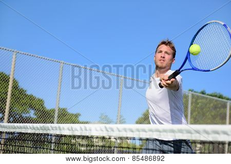 Tennis player man hitting ball in a volley. Male sport fitness athlete playing tennis on outdoors ha
