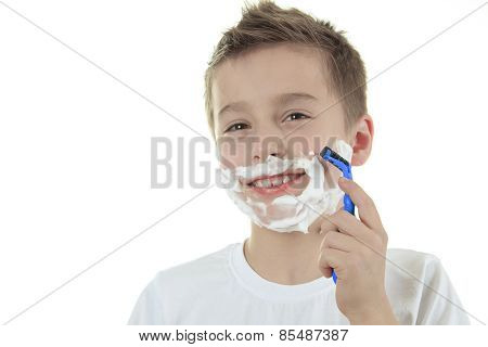playful little young boy shaving face over white