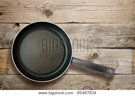 Frying Pan On Old Wooden Background