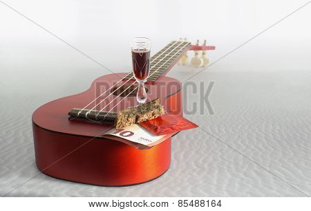 Guitar Ukulele, Bread,  Euro Banknote,  Glass With A Drink And Condom At Seaside