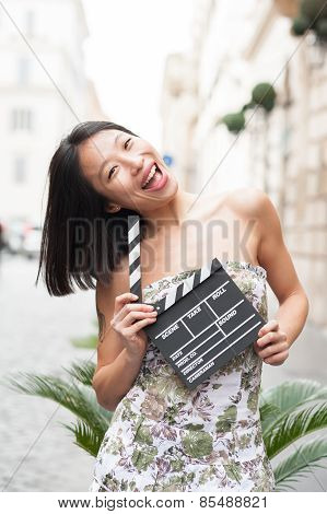 Young Asian Woman Smiling Shows Clapper Board