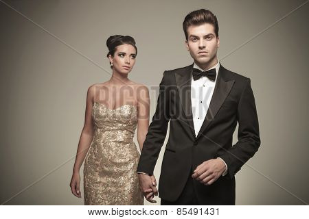 Handsome young elegant man holding his girlfriend by hand while she is looking away from the camera.