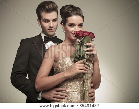 Beautiful elegant woman smelling a bunch of red roses while her husband is embracing her from the back.