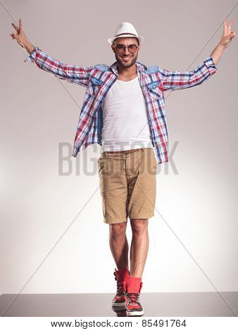 Happy young casual man walking while holding his hands up celebrating a victory.