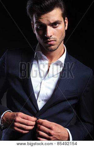 Close up picture of a handsome young business man closing his jacket while looking at the camera.