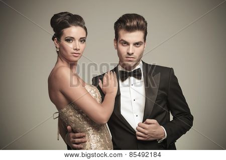 Close up picture of a young elegant couple posing embraced on sgrey studio background.