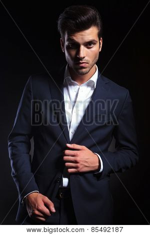 Portrait of a handsome young business man unbuttoning his jacket while looking at the camera.