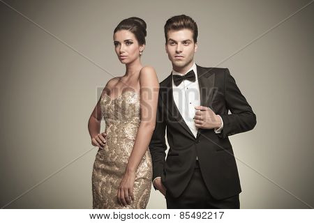 Side view of a elegant woman posing with her husband on grey studio background.