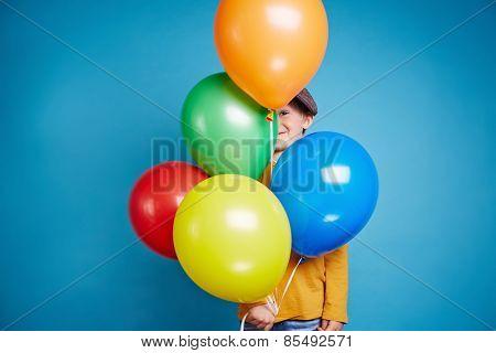 Portrait of a little boy holding balloons