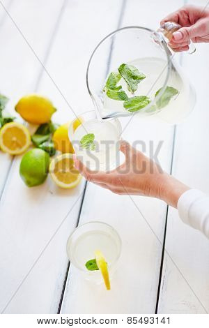 Female hands pouring water with mint for the cocktail