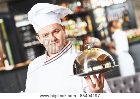 portrait of male cook chef at restaurant serving food with cloche lid
