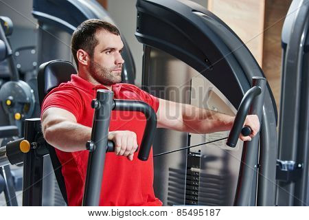 man doing excercises with weight training equipment on sport gym club
