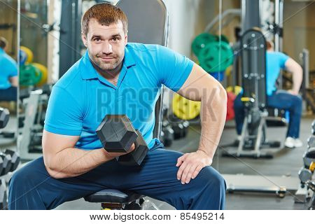 fitness man at biceps brachii muscles exercises with training dumbbells in gym