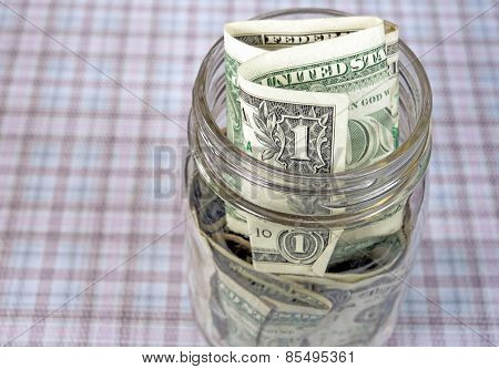 dollar bills in mason jar