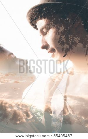 Double exposure portrait of tender couple combined with photograph of sunset