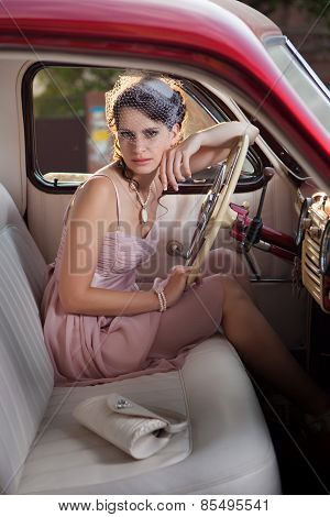 Pretty Woman Is Sitting In The Vintage Car.