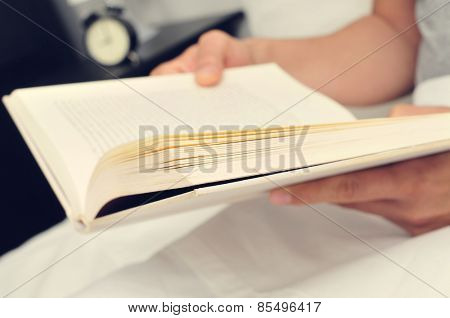 closeup of a young man reading a book in bed