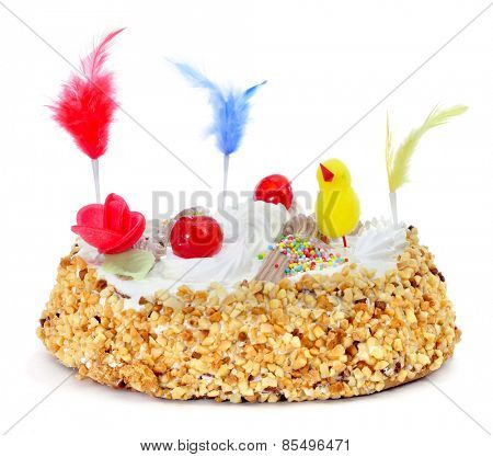 closeup of a mona de pascua, a cake eaten in Spain on Easter Monday, ornamented with feathers and a teddy chick, on a white background