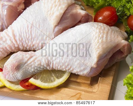 Raw chicken drumstick on the chopping board