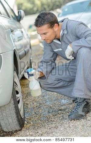 Mechanic washing a customer's car wheels