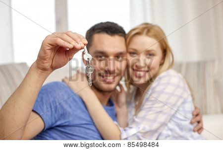 love, people, real estate, home and family concept - smiling couple showing keys over living room background