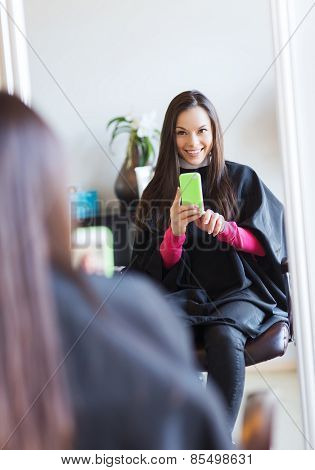beauty and people concept - happy young woman with smartphone taking mirror selfie at hair salon