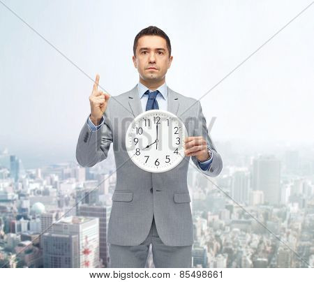 business, people, time management and gesture concept - businessman in suit holding clock showing 8 o'clock and pointing finger up over city background