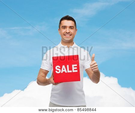 shopping, discount, consumerism, gesture and people concept - smiling man with red sale sigh showing thumbs up over blue sky and cloud background