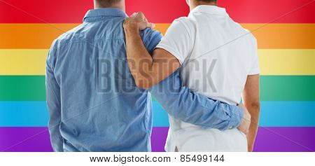 people, homosexuality, same-sex marriage, gay and love concept - close up of happy male gay couple or friends hugging from back over rainbow flag background